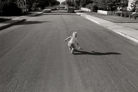 1977 Perfect Timing - Car at the end of the road is perfectly centered as the boy retrieves the ball.